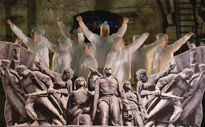 """Un ejército de trabajadores soviéticos interpretan juntos el himno partisano de Lenin. Belgrado contra el desmoronamiento de una época encarnada en el trabajador precario del realismo socialista. Cantan """"Quiero un nuevo cepillo de dientes"""", lucen un traje barato decentemente presentable y sus dientes son espeluznantes."""